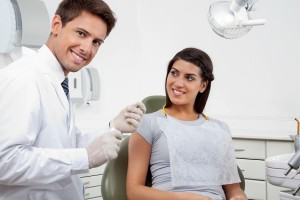 Happy Male Dentist Holding Thread While Patient Looking At Him