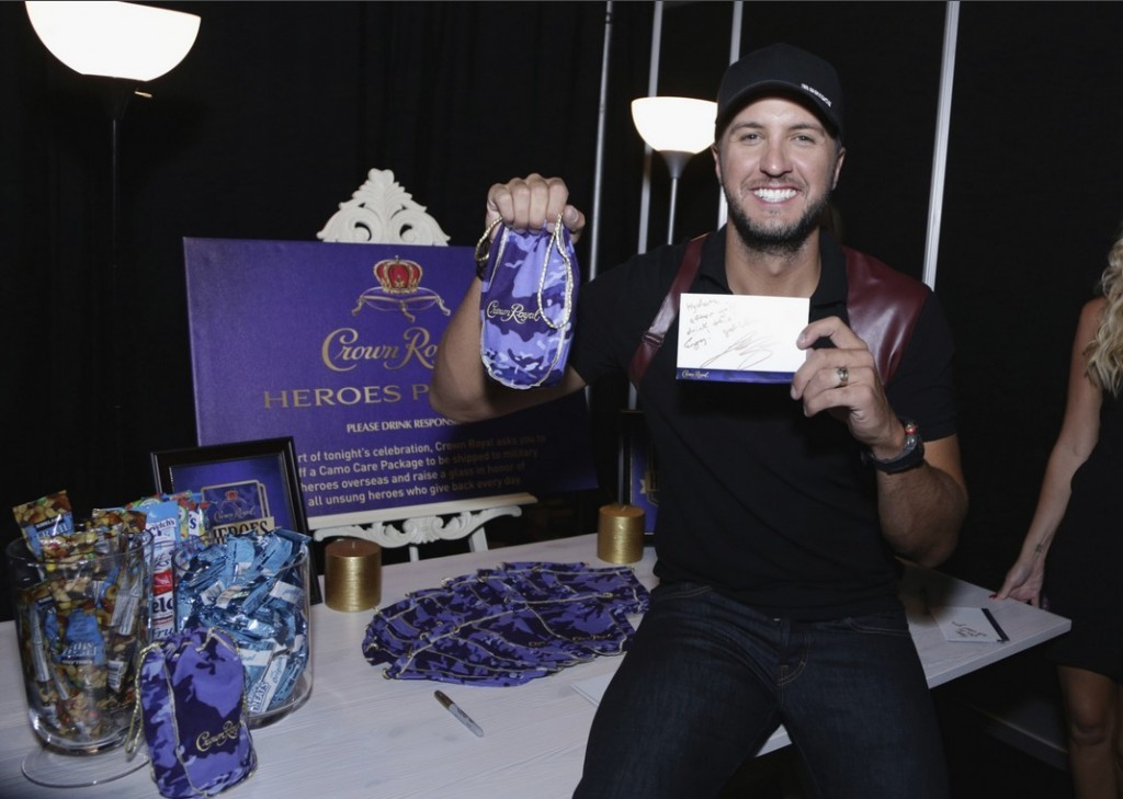 Musician Luke Bryan stuffs a Crown Royal CAMO care package to be sent to troops backstage at the 2015 CMT Awards at Bridgestone Arena on June 10, 2015 in Nashville, Tennessee. (Photo by Anna Webber/Getty Images for Crown Royal)